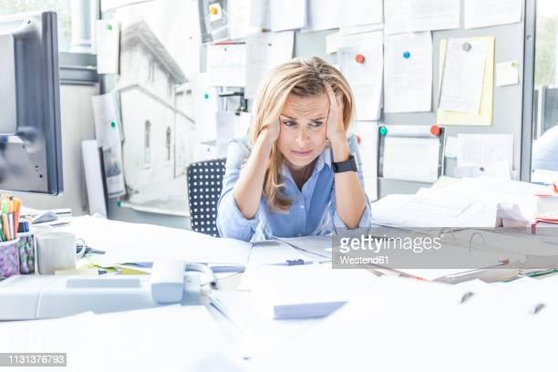 despaired woman sitting at desk in office surrounded by paperwork - omgeven stockfoto's en -beelden