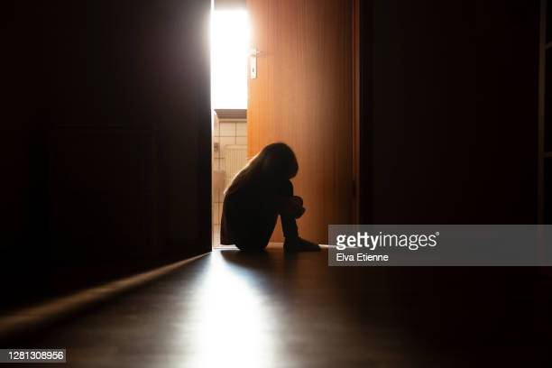 despairing child sitting with head on knees in the dark frame of a doorway, backlit by a room behind flooded with daylight - sadness stock pictures, royalty-free photos & images