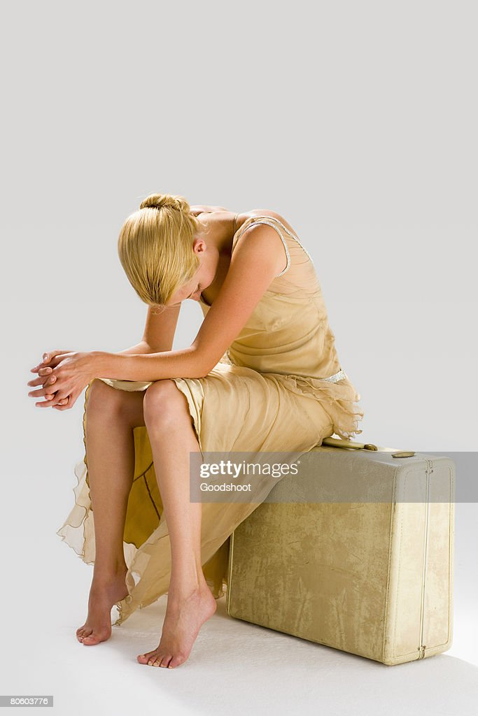 Despairing woman sitting on suitcase : Stock Photo