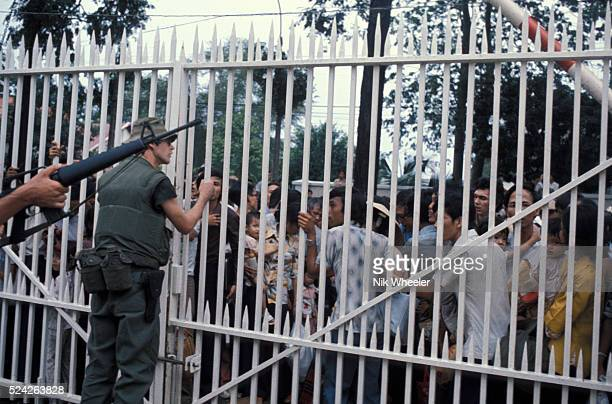 desperate and frightened South Vietnamese try to convince US Marines guarding the American Embassy to let them into the compound hoping that they...