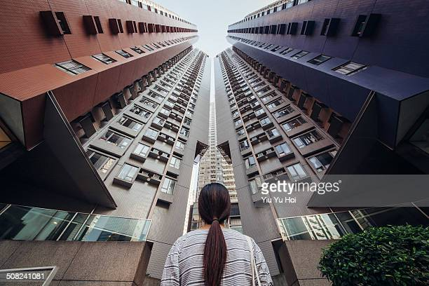 Desperate Asian female looking up at city jungle