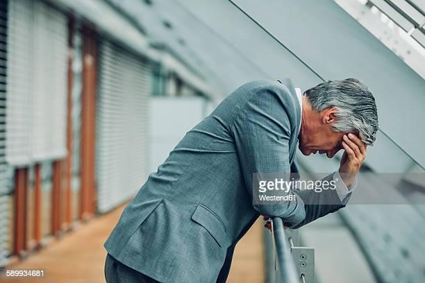 Desperate businessman leaning on railing