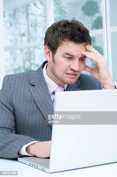 desperate businessman working with laptop computer