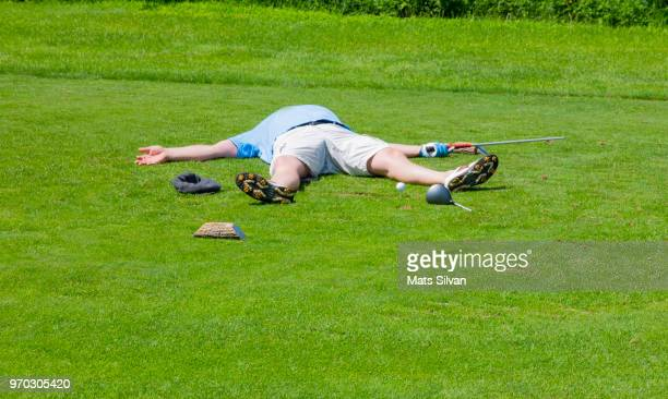 desperate golfer lying on the tee box with broken golf club driver - golftee stock-fotos und bilder