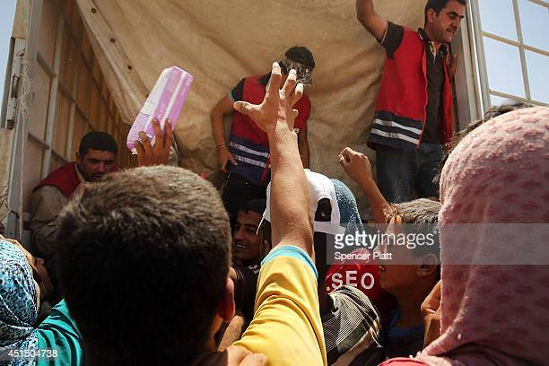 Desperate Iraqis at the Khazair displacement camp for those caughtup in the fighting in and around the city of Mosul wait for food and other items...