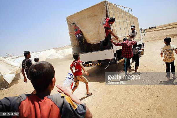 Desperate Iraqi's at the Khazair displacement camp for those caughtup in the fighting in and around the city of Mosul chase a Red Crescent society...