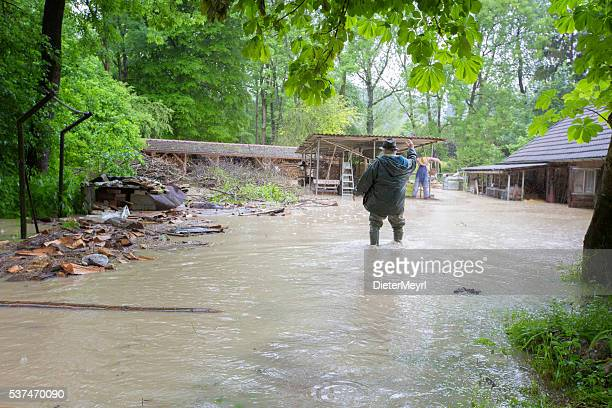 Desperate Man in front of Flooded House