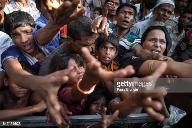 Desperate Rohingya grab for aid handouts of clothing and food on September 15 2017 in Tankhali Bangladesh Nearly 400000 Rohingya refugees have fled...