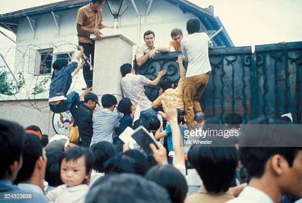 Desperate South Vietnamese citizens try to scale the walls of the American Embassy in a vain attempt to flee Saigon and avancing North Vietnamese...