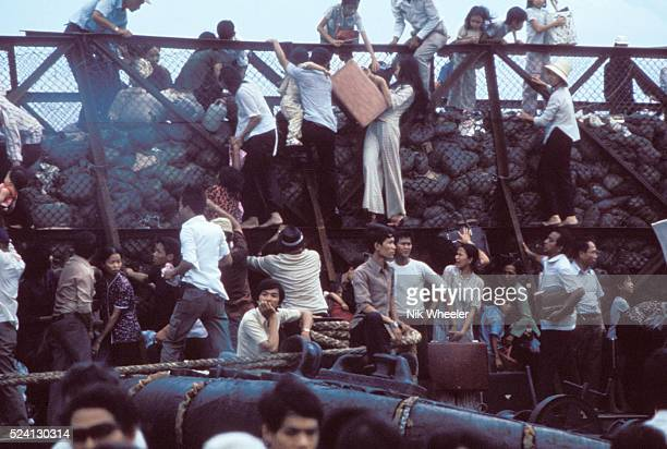 desperate South Vietnamese clamber aboard barges in the port of Saigon in an attempt to escape from advancing North Vietnamese troops on the day of...