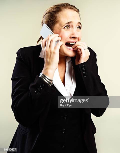 Desperate, stressed businesswoman on phone bites nails in panic