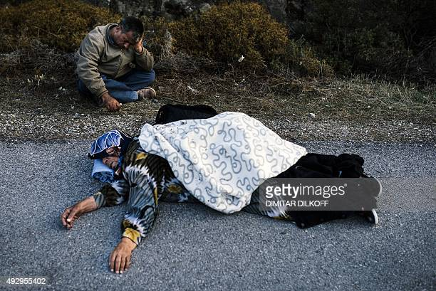 A desperate Syrian Kurdish man sits next to his mother who collapsed from exhaustion on the road after arriving on the Greek island of Lesbos after...