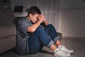 Desperate teen boy in dark room at home