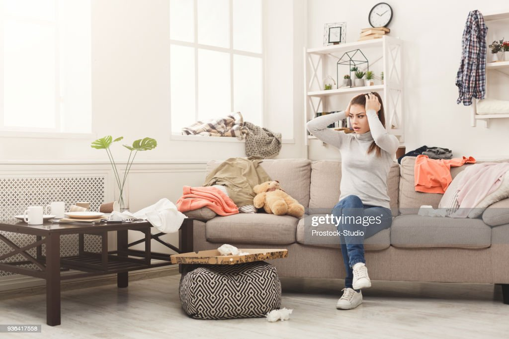 Desperate woman sitting on sofa in messy room : Stock Photo