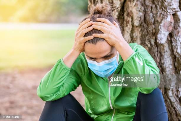 desperate woman sitting on the floor holding her hands wearing a protective mask - terrified stock pictures, royalty-free photos & images