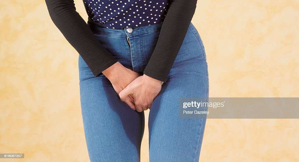 Desperate woman wetting herself : Stock Photo