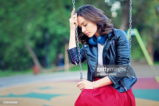 desperate young girl is sitting sad on the swing - relationship breakup stock pictures, royalty-free photos & images