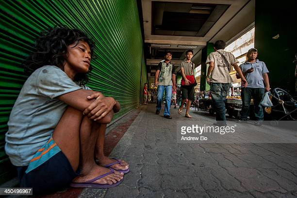 CONTENT] A desperate young homeless women sits begging for money in a street sidewalk in Quiapo district of Manila as passers by walk past The women...