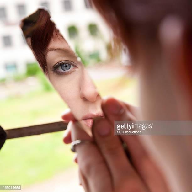 Verzweifelten jungen Frau auf der Suche in zerbrochenen Spiegel