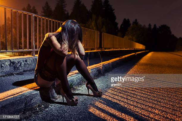 desperate young woman sitting on the bridge - prostitutie stockfoto's en -beelden