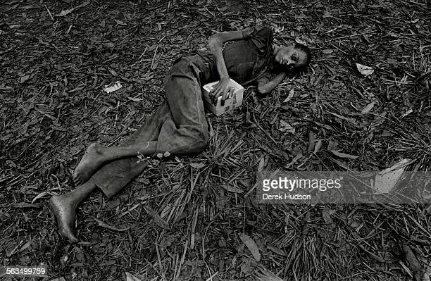 A desperately sick and emaciated young man lies on the leaf strewn jungle floor clutching a box of food aid near an aid centre set up by the French...