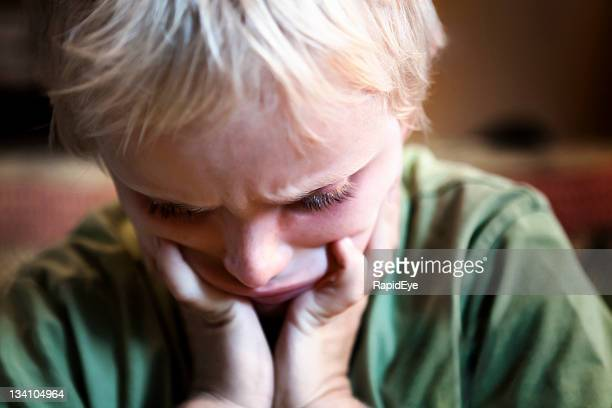 desperately unhappy 7 year old boy looks down - autism spectrum disorder stock photos and pictures
