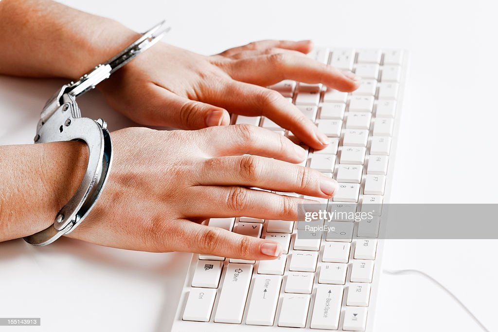 Despite being handcuffed hands type away busily on keyboard : Stock Photo