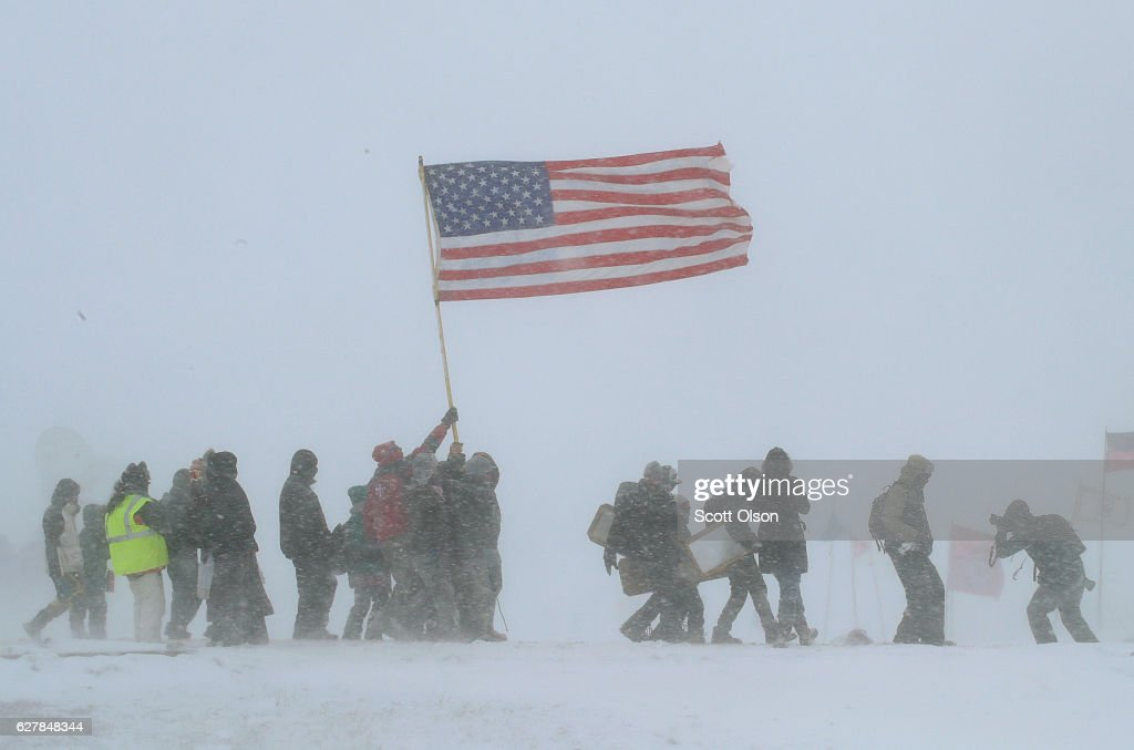 Despite blizzard conditions, military veterans march in support of the 'water protectors' at Oceti Sakowin Camp on the edge of the Standing Rock Sioux Reservation on December 5, 2016 outside Cannon Ball, North Dakota. Over the weekend a large group of military veterans joined native Americans and activists from around the country who have been at the camp for several months trying to halt the construction of the Dakota Access Pipeline. Yesterday the US Army Corps of Engineers announced that it will not grant an easement for the pipeline to cross under a lake on the Sioux Tribes Standing Rock reservation. The proposed 1,172-mile-long pipeline would transport oil from the North Dakota Bakken region through South Dakota, Iowa and into Illinois.