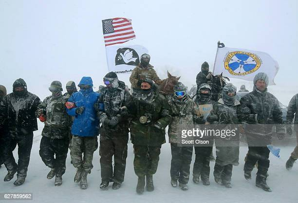 "Despite blizzard conditions, military veterans march in support of the ""water protectors"" at Oceti Sakowin Camp on the edge of the Standing Rock..."