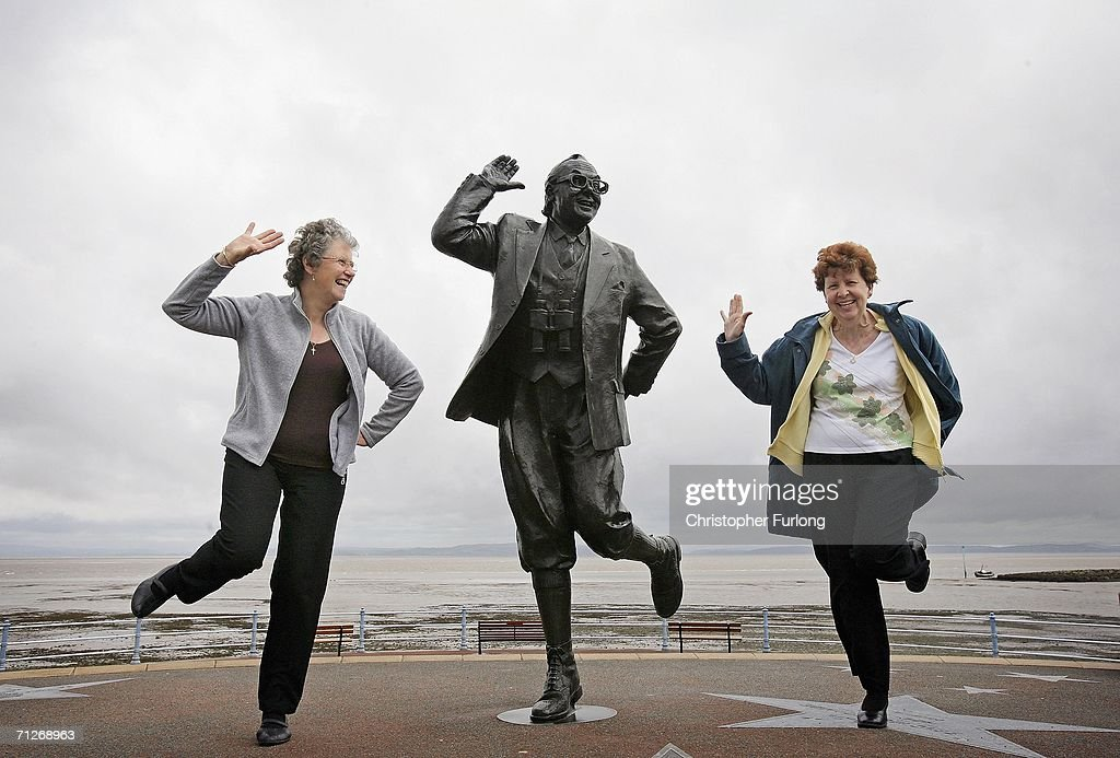 Despite inclement weather members of Dover and Deal Odd Fellows Club sing 'Bring me sunshine' and raise a happy smile as they perform the famously British dance of comedians Morcambe and Wise, next to a statue of Eric Morcambe at Morcambe Bay on June 22, 2006, in Morcambe, England. Confidence & Happiness specialist, Scientist Cliff Arnall from the University of Cardiff has identified June 23, 2006 as being the happiest day of the year. His calculations were based on outdoor activity, nature, social interaction, childhood summers, positive memories, temperature and holidays.