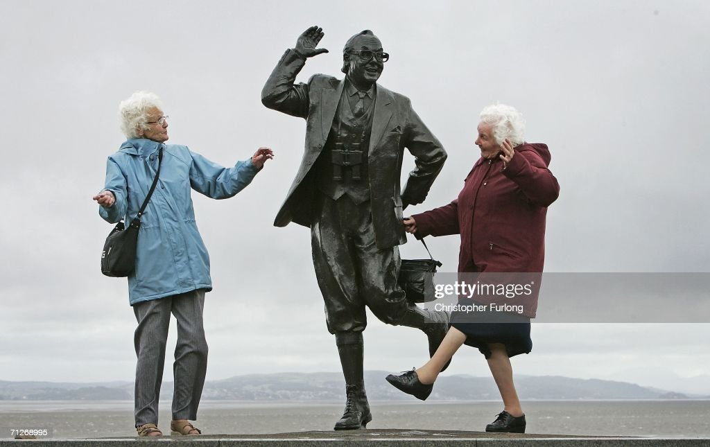 Despite inclement weather pensioners raise a happy smile as they perform the famously British dance of comedians Morcambe and Wise next to a statue of Eric Morcambe, at Morcambe Bayon June 22, 2006, in Morcambe, England. Confidence & Happiness specialist, Scientist Cliff Arnall from the University of Cardiff has identified June 23, 2006 as being the happiest day of the year. His calculations were based on outdoor activity, nature, social interaction, childhood summers, positive memories, temperature and holidays.