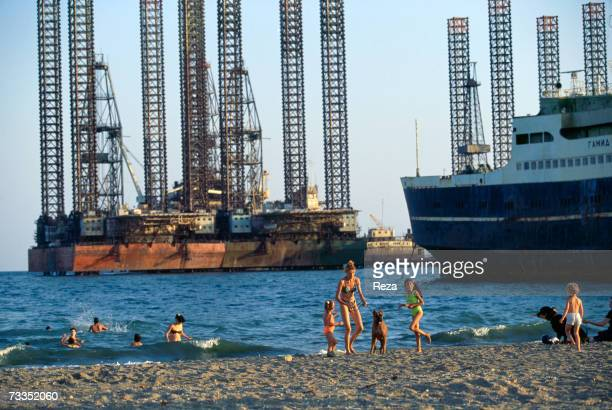 Despite pollution from the region's petrochemical industry Russian women and children bathe on the shore of the Caspian Sea just adjacent to looming...