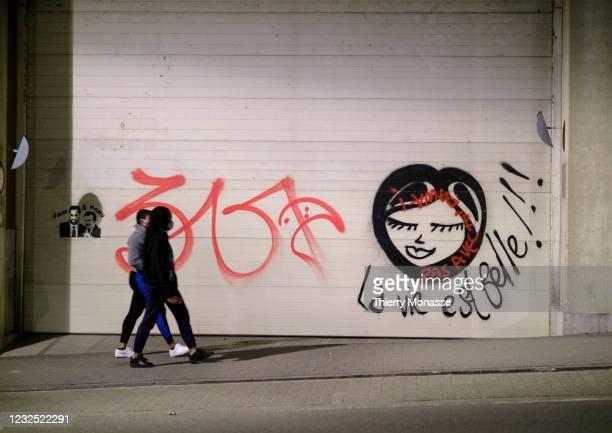 Despite the Coronavirus curfew 2 women are walking beside a graffiti where it is written 'La vie est belle' on the garage door of the Breydel bulding...