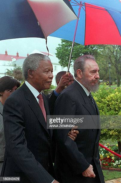 Despite the rain Cuban President Fidel Castro and South African President Nelson Mandela stroll through the gardens of Tuynhuis in Cape Town 04...