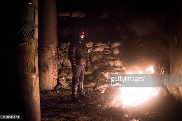 Despite the resignation of prime minister Mikola Az����rov ukranian protester spend the night at barricades In the picture a protester warms up next...