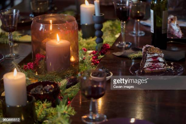 Dessert and wineglasses on illuminated dining table during Christmas