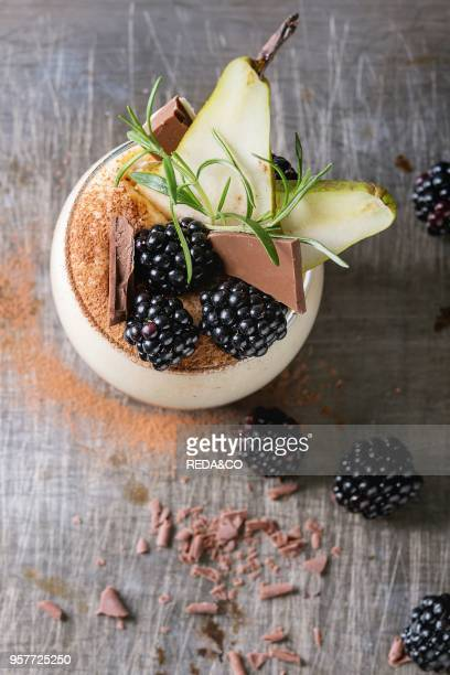 Dessert breakfast layered chia seeds chocolate pudding rice porridge in glass decorated by fresh blackberries sliced pear cocoa powder Stand with...