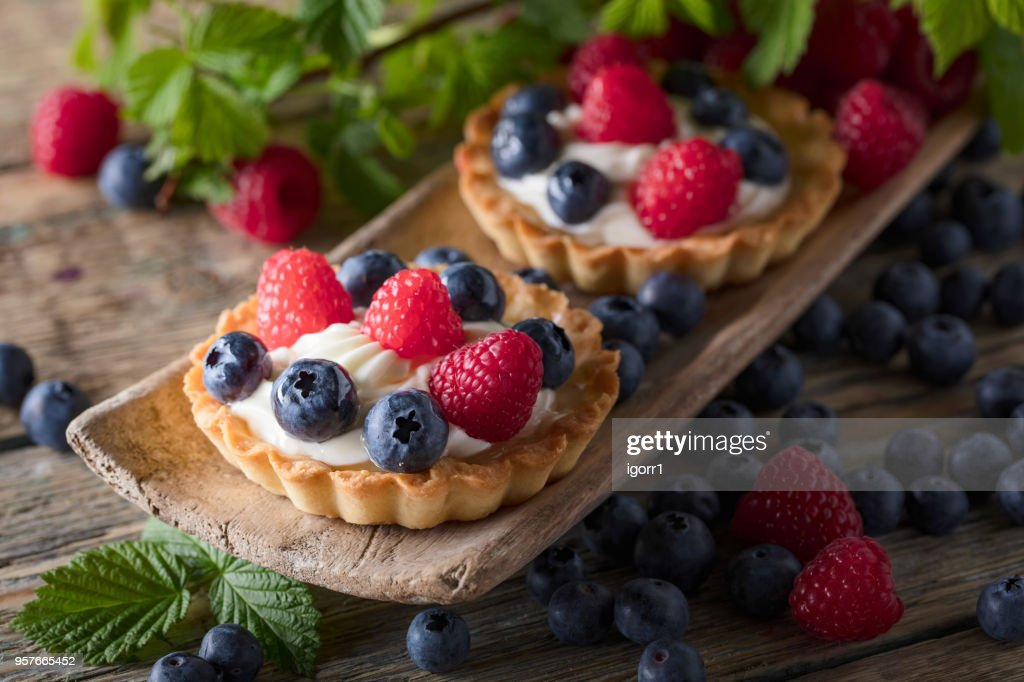 Dessert tarts with raspberries and blueberries on a wooden table. : Stock Photo