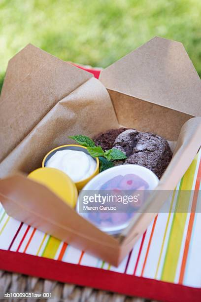Desserts in a container ready to be eaten sitting on a picnic basket