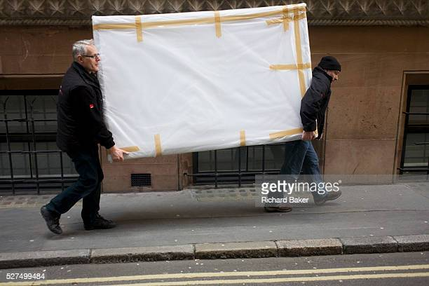 Destined for nearby offices two workmen deliver a heavy piece of corporate art taped up and covered in a narrow side street in the City of London the...