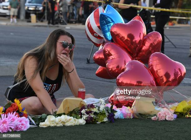 TOPSHOT Destiny Alvers who attended the Route 91 country music festival and helped rescue her friend who was shot reacts at a makeshift memorial on...