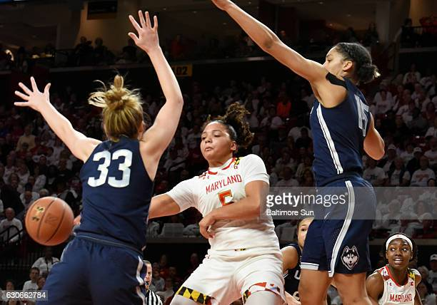 Destiny Slocum passes the ball around Connecticut's Katie Lou Samuelson and Gabby Williams in the first half at the Xfinity Center in College Park Md...