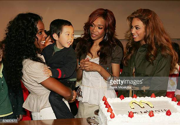 Destinys Child members Beyonce Knowles Kelly Rowland and Michelle Williams share a laughter with a 5yearold Japanese boy Ayuto Yokota during their...