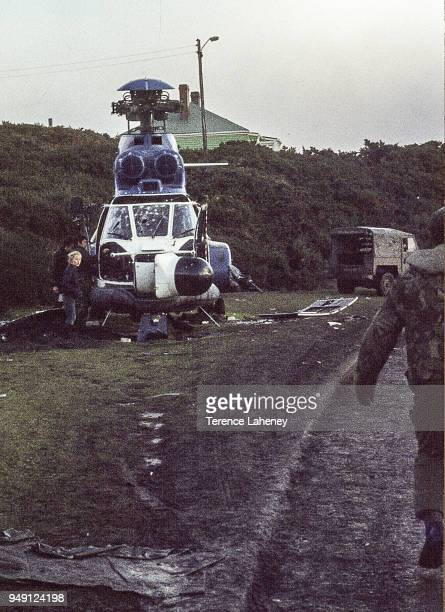 Destroyed Argentinian helicopter outside Government House in Port Stanley with local children investigating after the recapture of Port Stanley by...