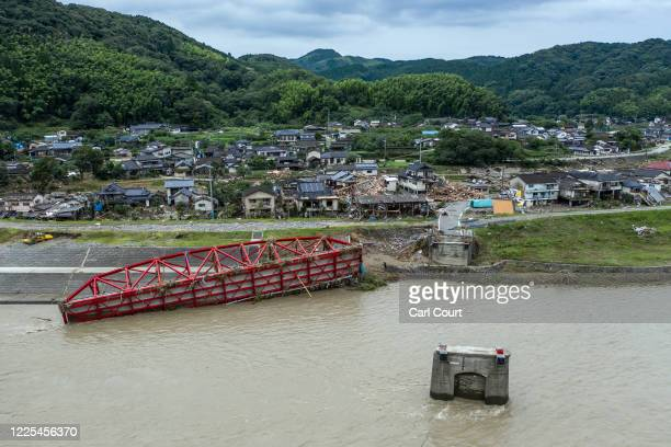 Destroyed bridge lies in the water next to a ruined village after the Kuma River flooded during torrential rain, on July 8, 2020 in Kuma, Japan....