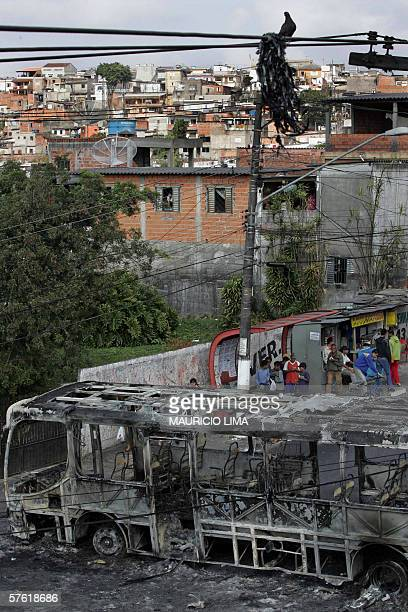 A destroyed bus burned by gang members during the night blocks a street in Campo Limpo neighborhoodsouth area of Sao Paulo Brazil 15 May 2006 Gangs...