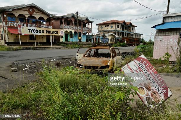 A destroyed car and buildings in a small town on the main highway on May 11 2019 near Buea These towns were attacked by the military as suspected...
