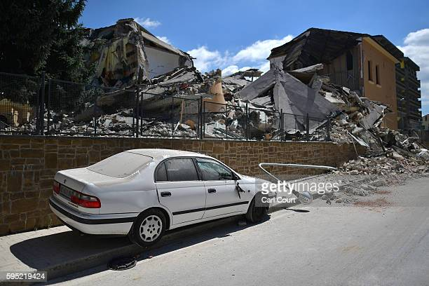 Destroyed car is parked next to a partially collapsed school that was built after the introduction of anti-earthquake construction legislation on...