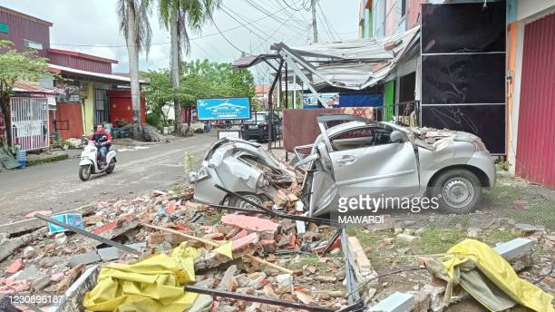 Destroyed car sits amongst debris on the side of a street in Mamuju on January 15 after a 6.2-magnitude earthquake rocked Indonesia's Sulawesi island.