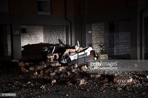 A destroyed car stands under a partially damaged buldng on October 31 a day after a 66 magnitude earthquake hit central Italy It came four days after...
